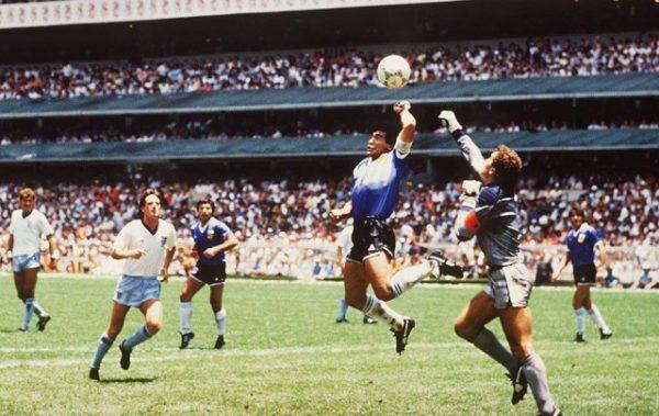 """La """"main de Dieu"""" de Maradona pendant la Coupe du Monde. L'athlète marque un but volontairement avec la main, contre l'Angleterre lors du quart de finale de la Coupe du monde 1986, le 22 juin, dans le stade Azteca de Mexico (Mexique). On peut voir le footballeur dans les airs, avec la main en direction du ballon."""