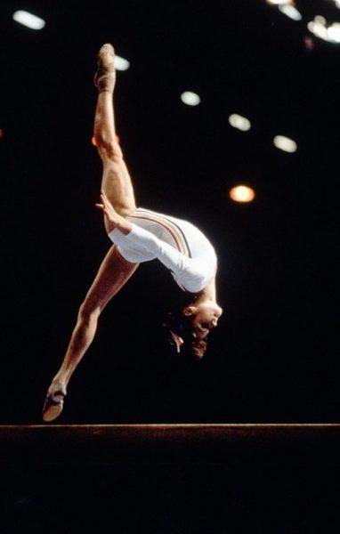gymnaste Nadia Comaneci JO histoire du sport. La sportive effectue un salto arrière sur les barres asymétriques.