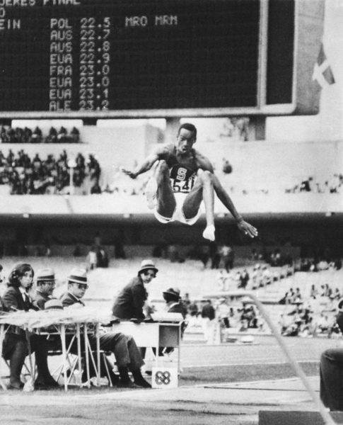 En 1968, Bob Beamon effectue le record mondial du saut, avec une hauteur de 8,9 mètres. Sur cette image, l'athlète est dans les airs avec un air de surprise sur son visage.