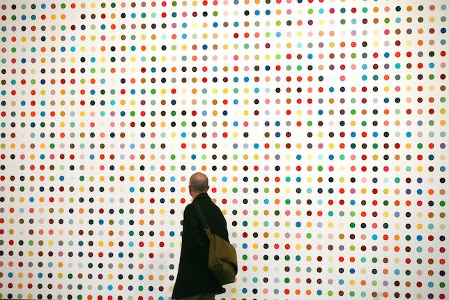 A man studies one of Damien Hirst's Spot Paintings