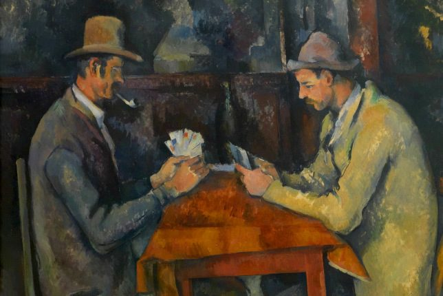 Paul Cézanne painting of two farmers with hats and coats playing cards around a table
