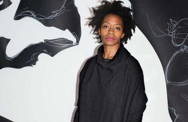 Portrait of Kara Walker with one of her mural artworks