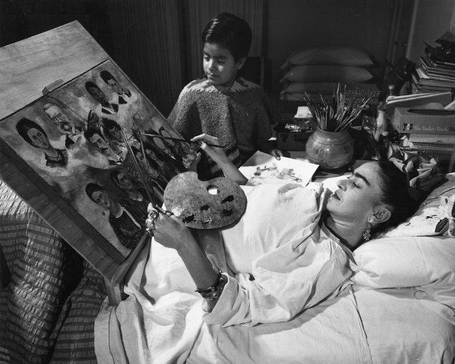 Photographie de Frida Kahlo en train de peindre dans son lit