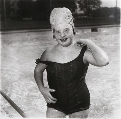 Photographie en noir et blanc, prise en 1990 par l'artiste Diane Arbus, intitulée « Girl in a Swimming Cap ». Une petite fille handicapée mentale, vêtue de son maillot de bain une pièce et de son bonnet de bain, se tient debout dans la piscine et nous adresse un grand sourire.
