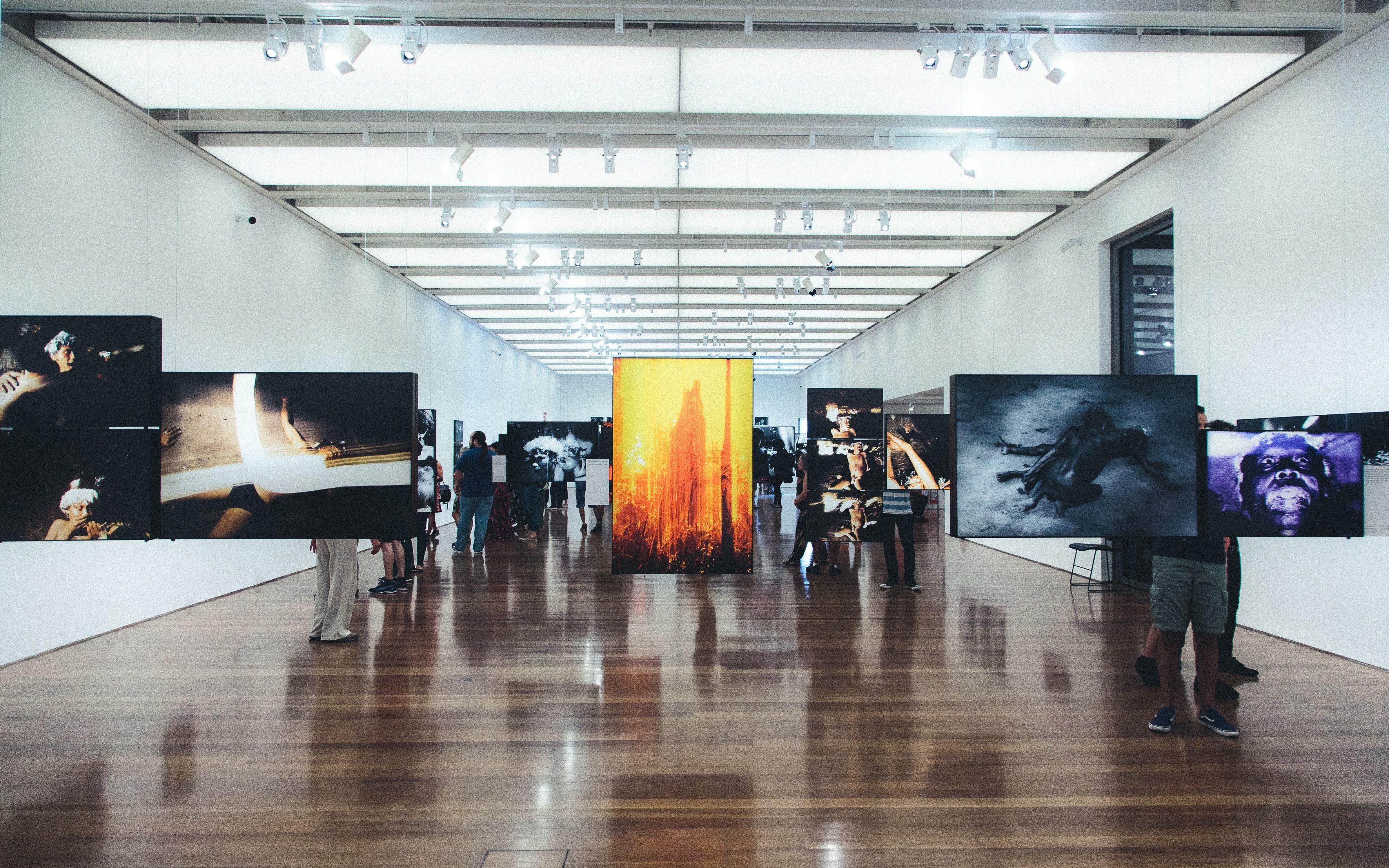 Salle d'exposition remplie de visiteurs.