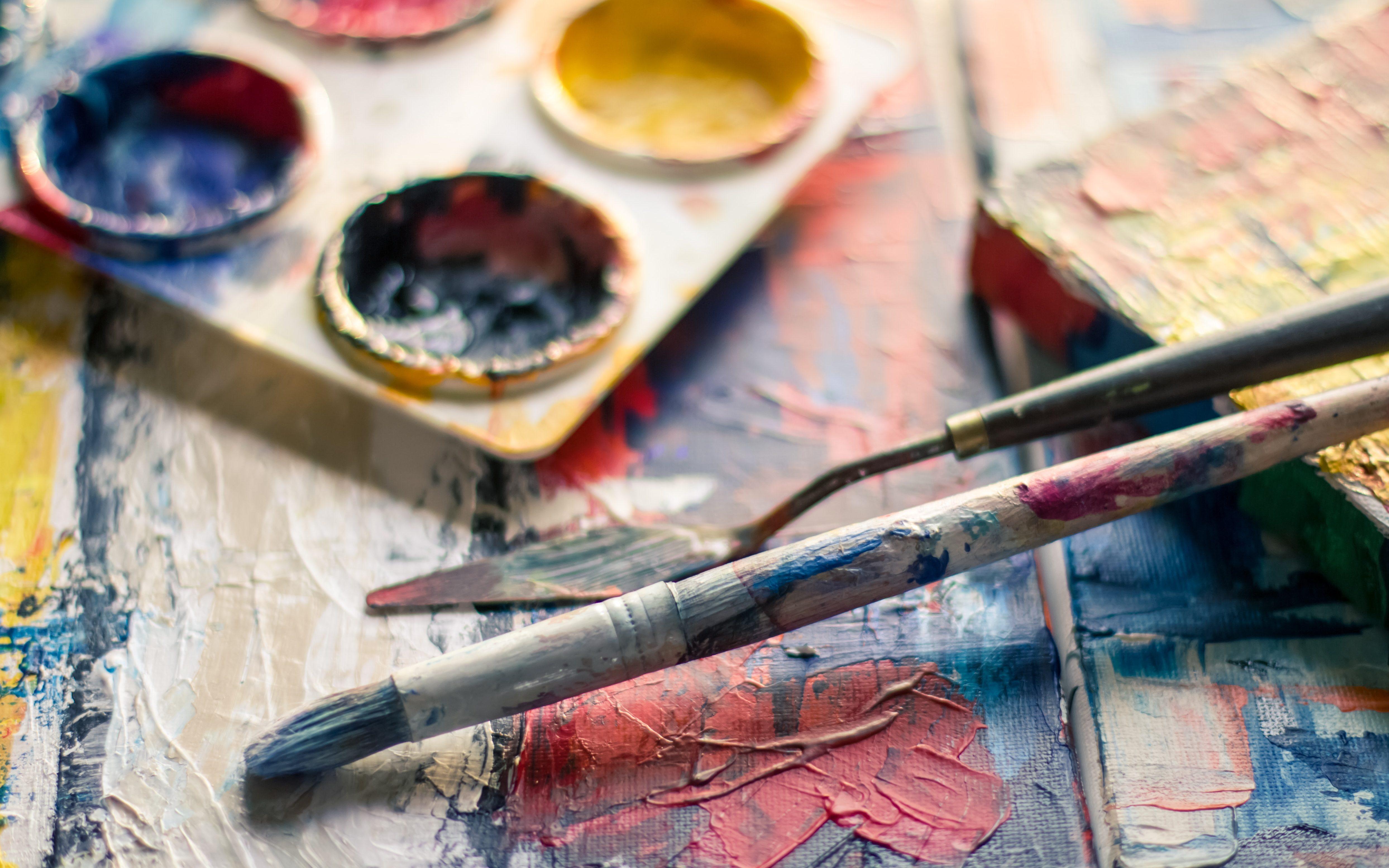 Photographie d'une palette de peintures et de pinceaux.