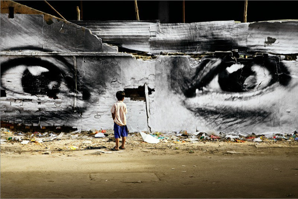 "Color photograph, taken in Cambodia in 2009 by the street-artist JR. Entitled ""28 Millimeters, Women Are Heroes"", this photograph was taken during an action in Phnom Penh, Peng Panh. It shows us a little boy facing a huge piece of dilapidated wall, on which JR's collage appears: the black and white eyes of a woman. The floor is strewn with garbage. Socially engaging photography."