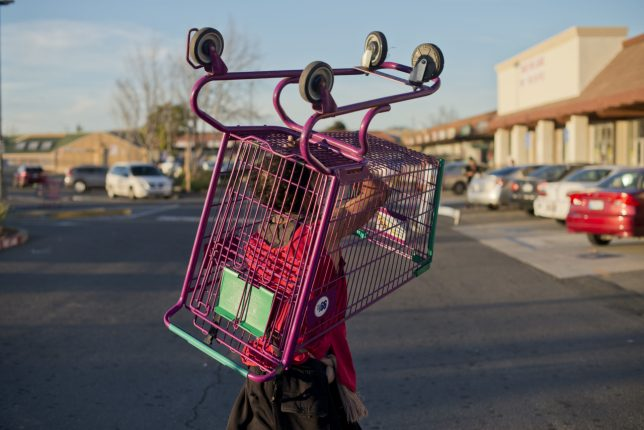 "Color photograph, taken by Carolyn Drake, of a volunteer returning a pink and green cart in the parking lot of the ""99 cents"" store on Sonoma Boulevard. Socially engaged photography."