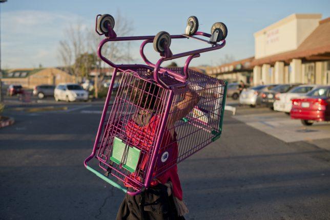 Photographie en couleurs, prise par Carolyn Drake, représentant un bénévole qui rapporte un chariot rose et vert sur le parking du magasin « 99 cents » sur Sonoma Boulevard.