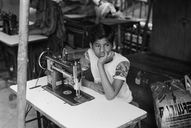 "Black and white photograph, taken by Samuel Cueto in 2018, entitled ""Dreamer"". A young teenager is sitting in front of a sewing machine, looking lost and dreaming. Socially engaging photography."