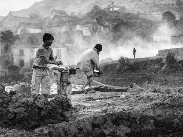 "Black and white photograph, taken by Pierrot Men in the city of Fianarantsoa, Madagascar, in 2016, as part of his ""Bricks Series"". Here, two men continue to shape bricks despite the storm. Socially engaging photography."