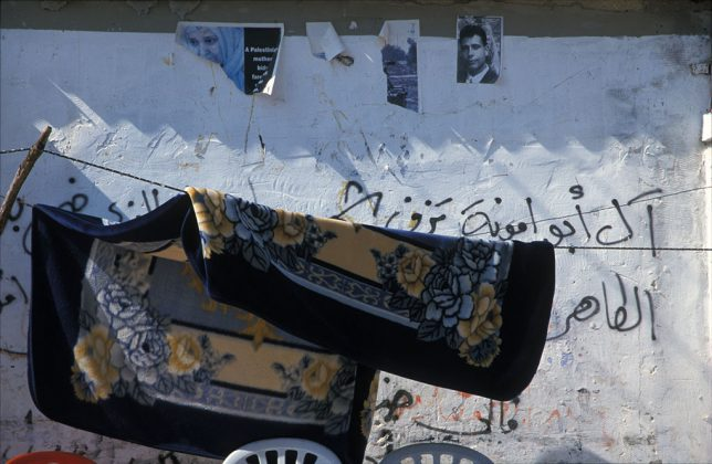 "Photograph by Taysir Batniji, untitled, included in his collection ""Walls of Gaza"". Taken in 2001, it is part of a series of 57 color photographs. In this photograph we can see a fabric stretched out on two threads, drying in the sun in the deserted streets of Gaza. Below, two white plastic chairs. Behind, a large white wall, on which one can see portraits of the ""disappeared"", ""martyrs"" and ""victims"". Socially engaging photography."
