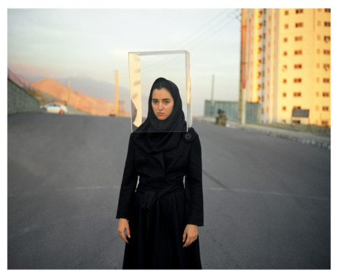 Color photograph, taken by Newsha Tavakolian, in the capital of Iran, Tehran. On this parking lot, a young woman covered with her black hijab is looking at us. A Plexiglas cube encloses her face. Behind her, a building, a car, and in the distance the desert and the mountains. Socially engaging photography.
