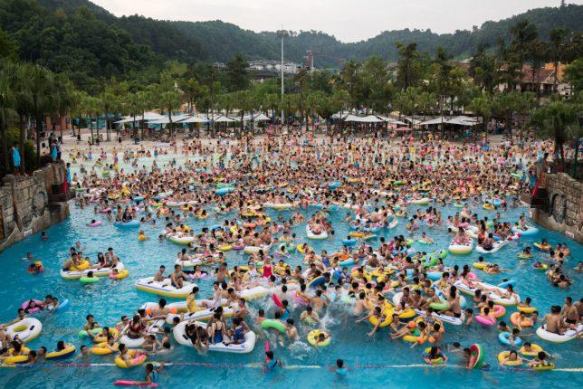 Photographie en couleurs, prise par Sim Chi Yin, représentant des vacanciers chinois de tous horizons s'entassant dans la piscine à vagues du parc aquatique des Caraïbes de Chongqing.