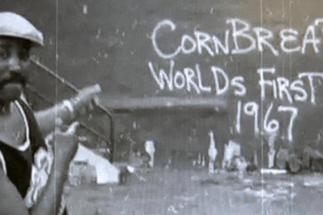 "Cornbread street artist posing alongside some graffiti reading ""Cornbread world's first 1967"""